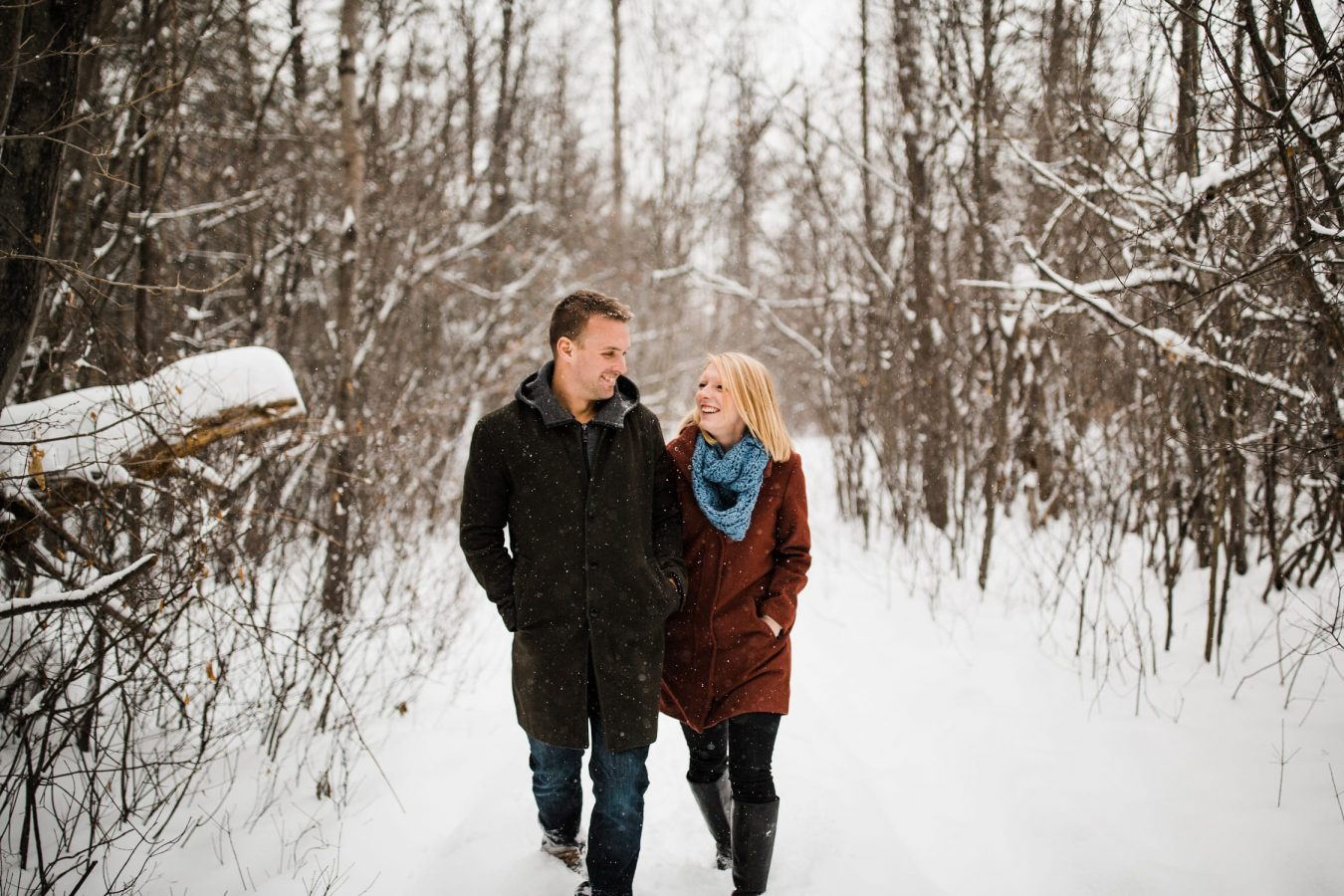 Couple walk a snowy pathway together