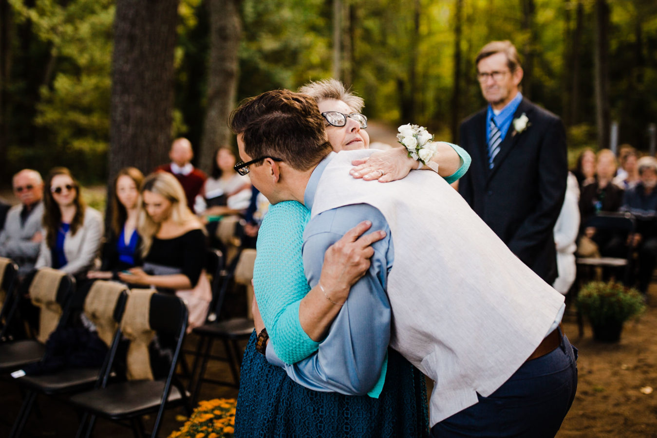 groom hugs his mother during wedding ceremony