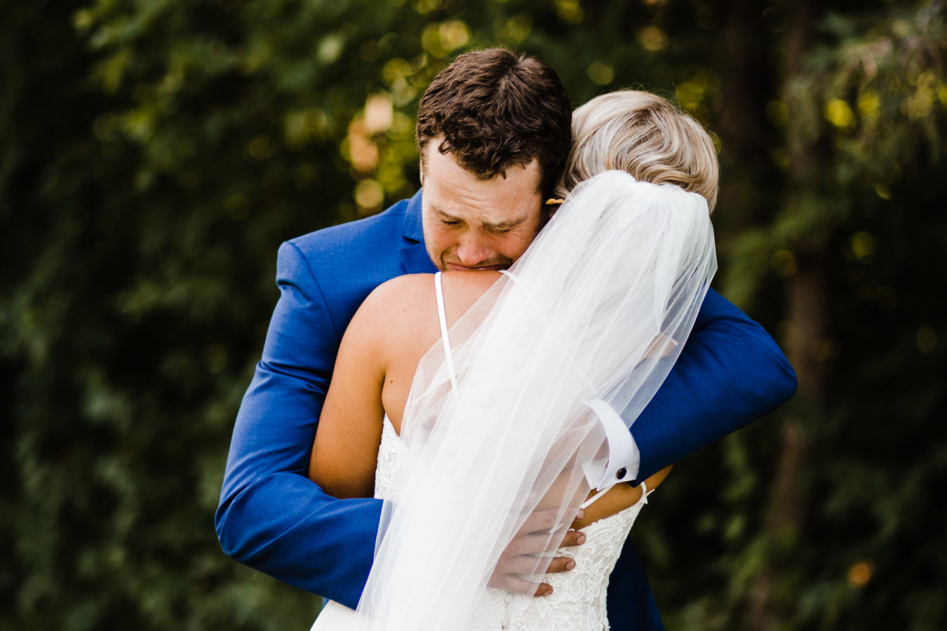 groom cries as he hugs his bride