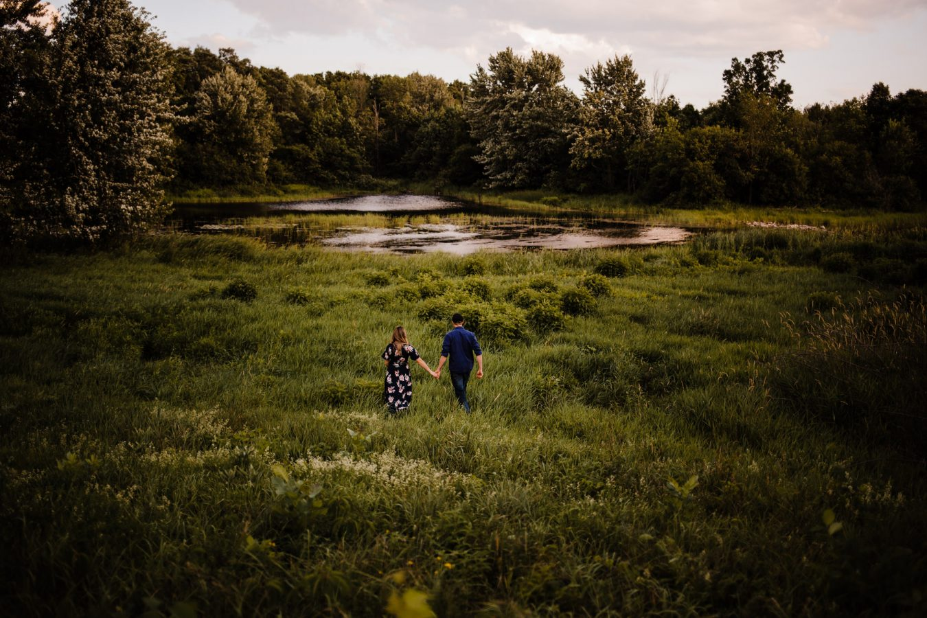 couple walk through tall grass towards water