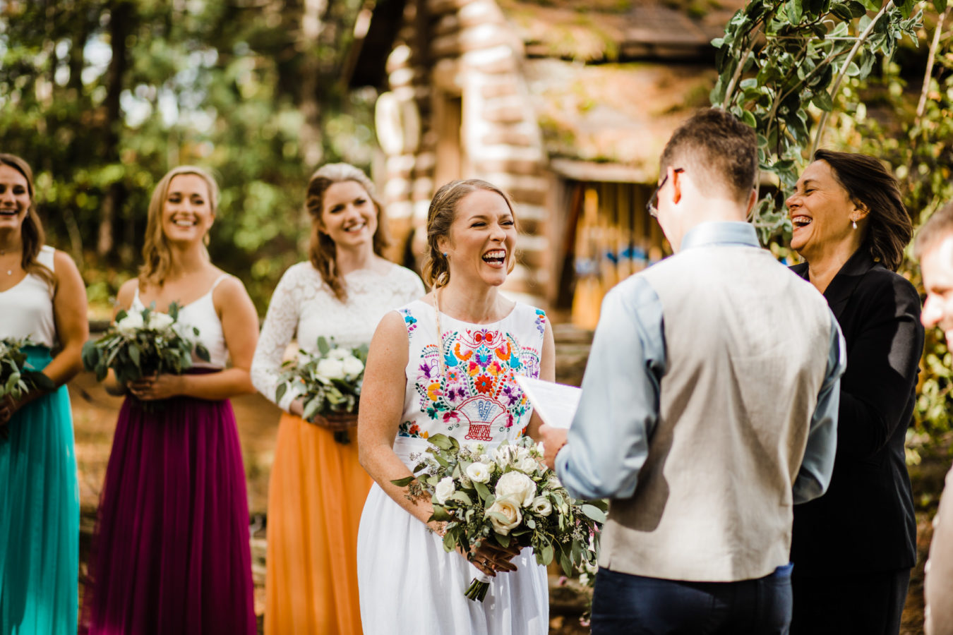 bride laughs during vows at oudoor ceremony