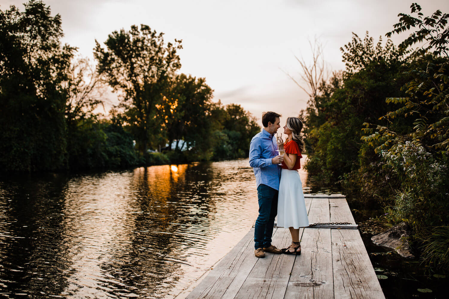 couple drink wine by river - merrickville engagement - carley teresa photography