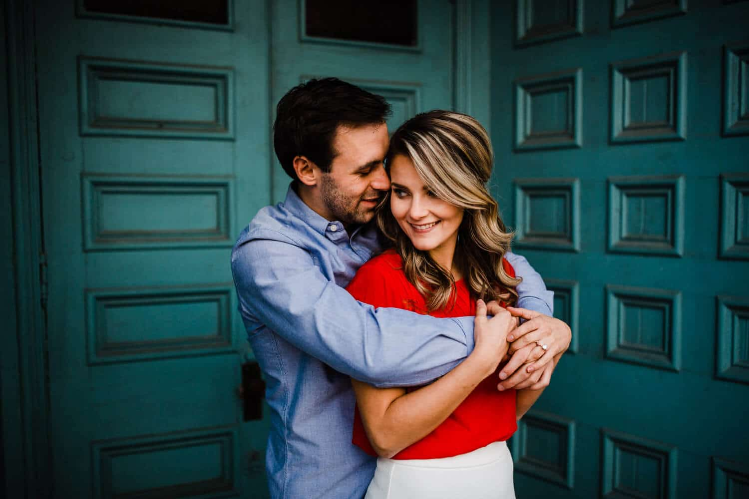 couple embrace in front of teal church doors - merrickville engagement - carley teresa photography