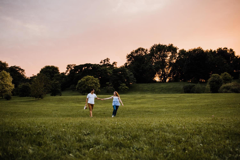 couple walk through open field at sunset - ottawa wedding photographer - carley teresa photography