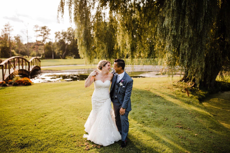 married couple walk by willow tree - ottawa wedding photographer - carley teresa photography