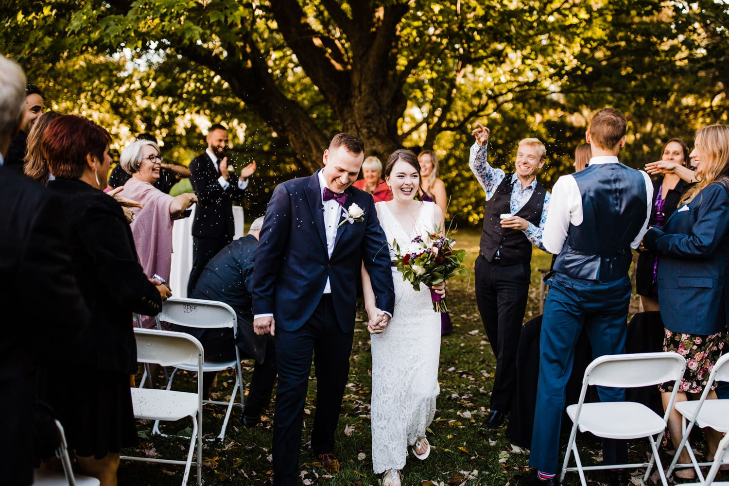 bride and groom leave ceremony as guests throw lavender - ottawa wedding photographer - carley teresa photography