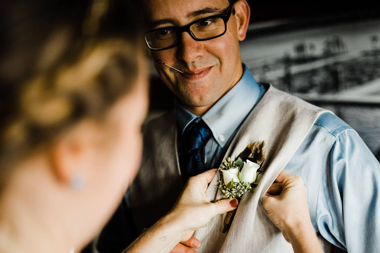 bride fixes groom's boutonnierre - ottawa wedding photographer - carley teresa photography