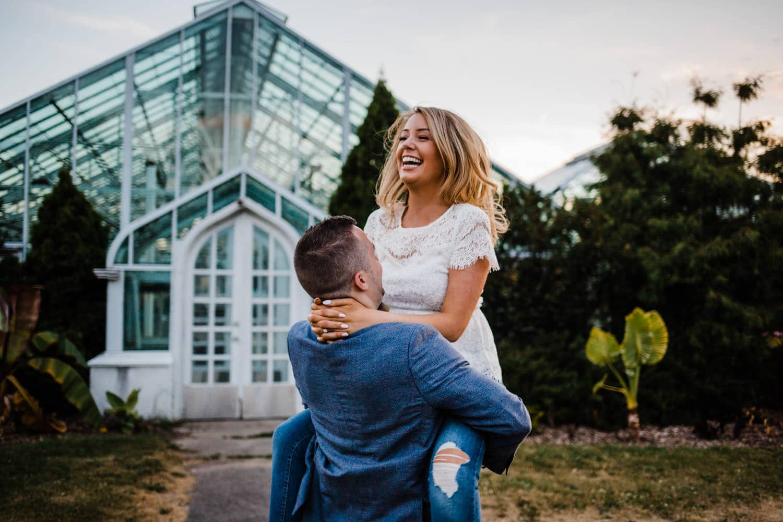 man lifts woman up into the air - ottawa wedding photographer - carley teresa photography