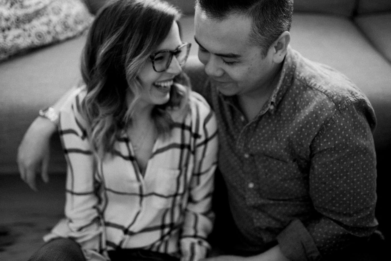 couple laugh together in living room - ottawa winter engagement photos