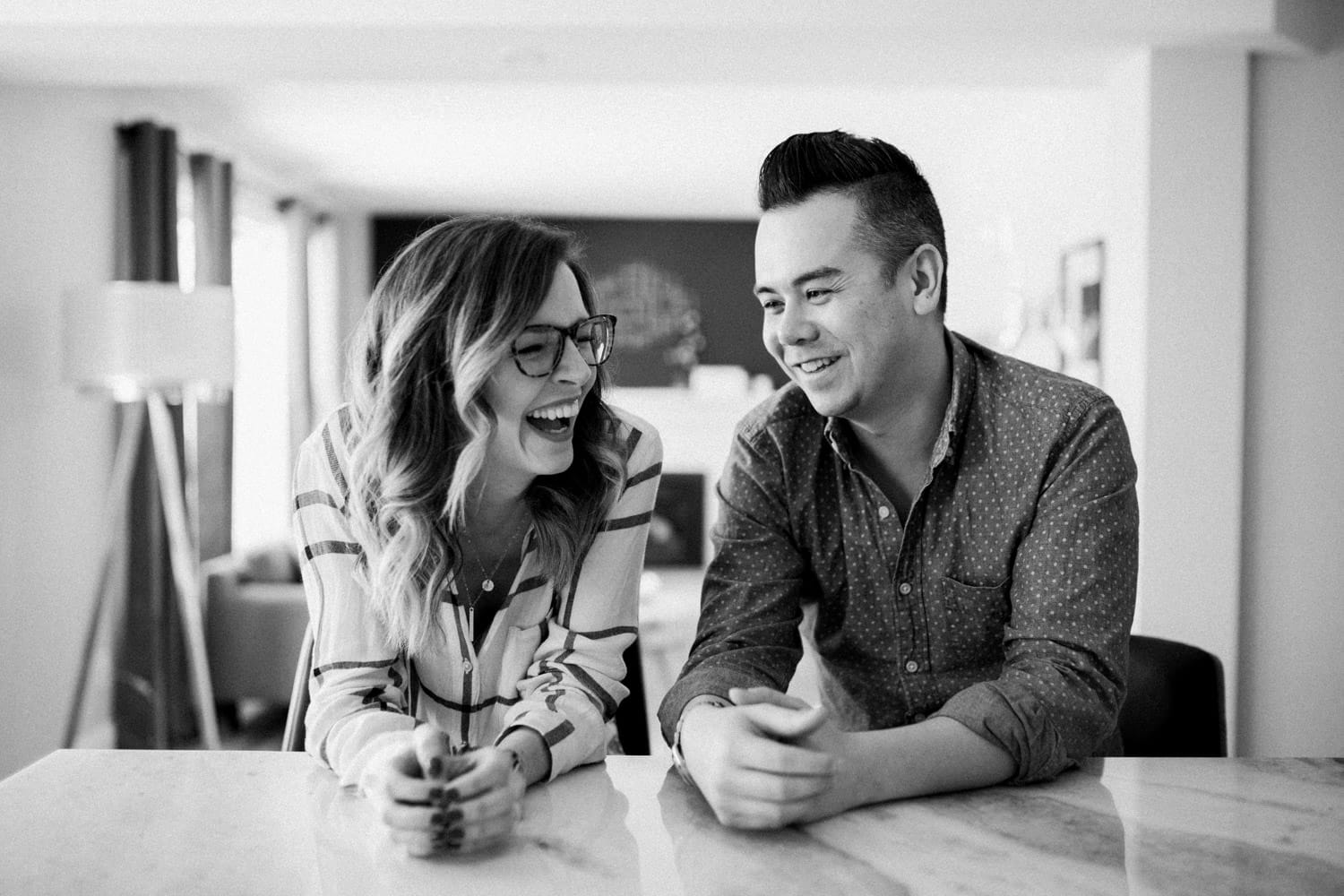 couple laugh together in kitchen - ottawa winter engagement photos