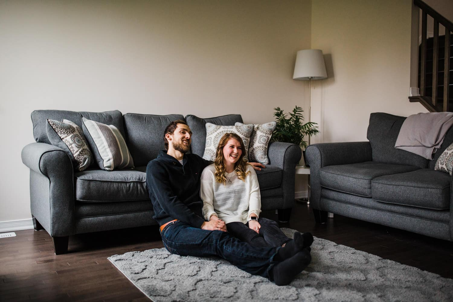 couple laugh at home together - ottawa winter engagement photos