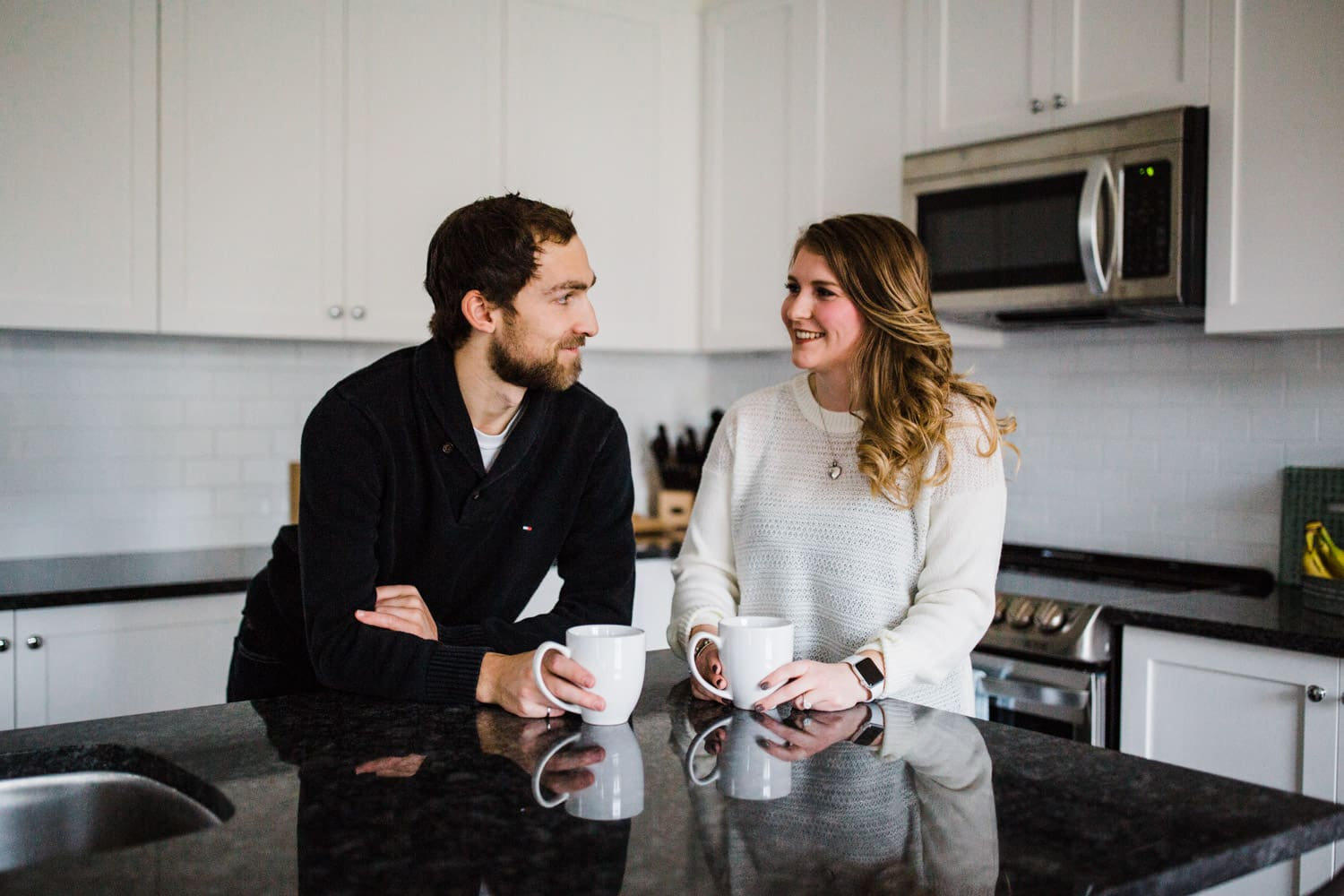 couple have a coffee in kitchen together - ottawa winter engagement photos