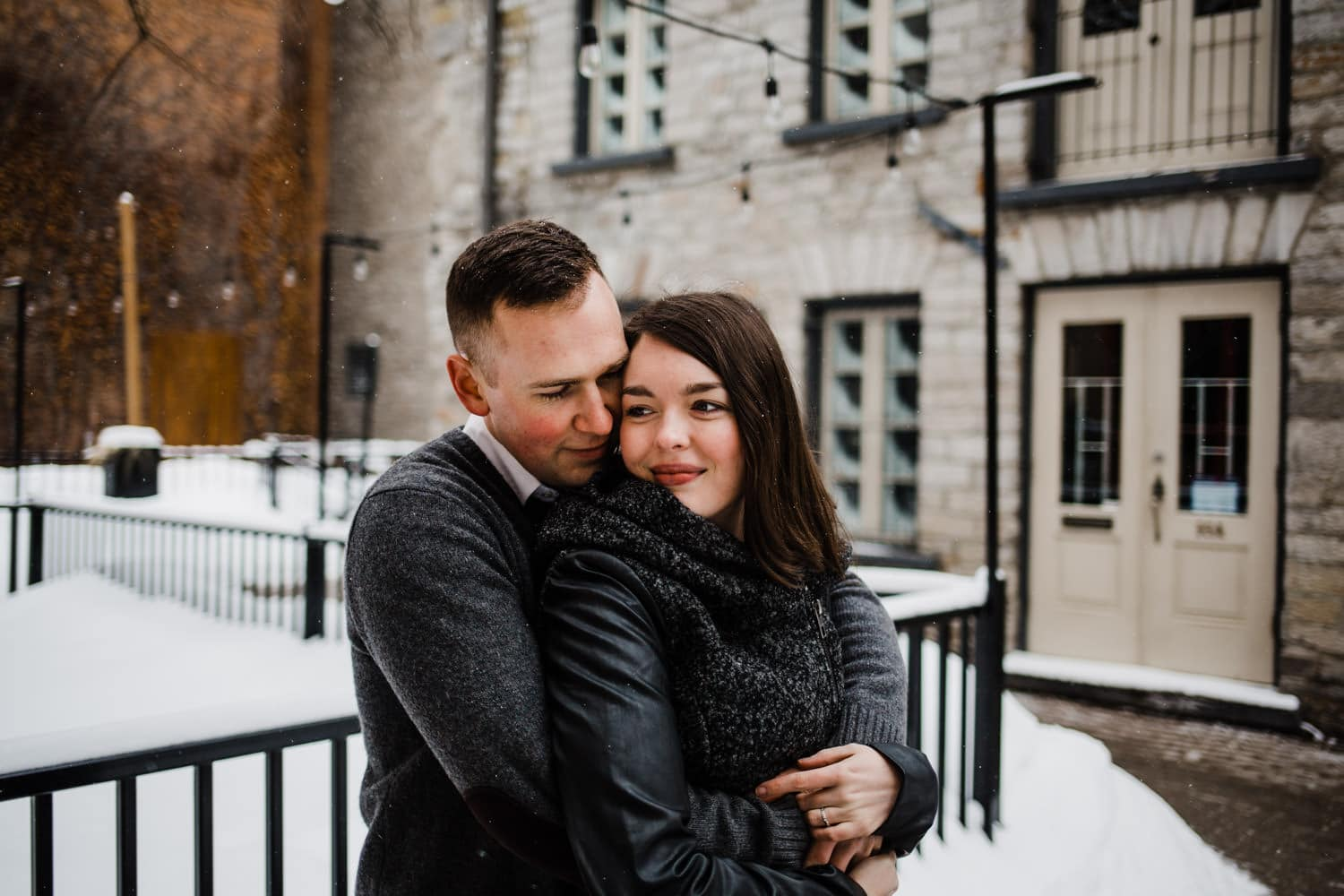 couple hug in byward market - ottawa winter engagement photos