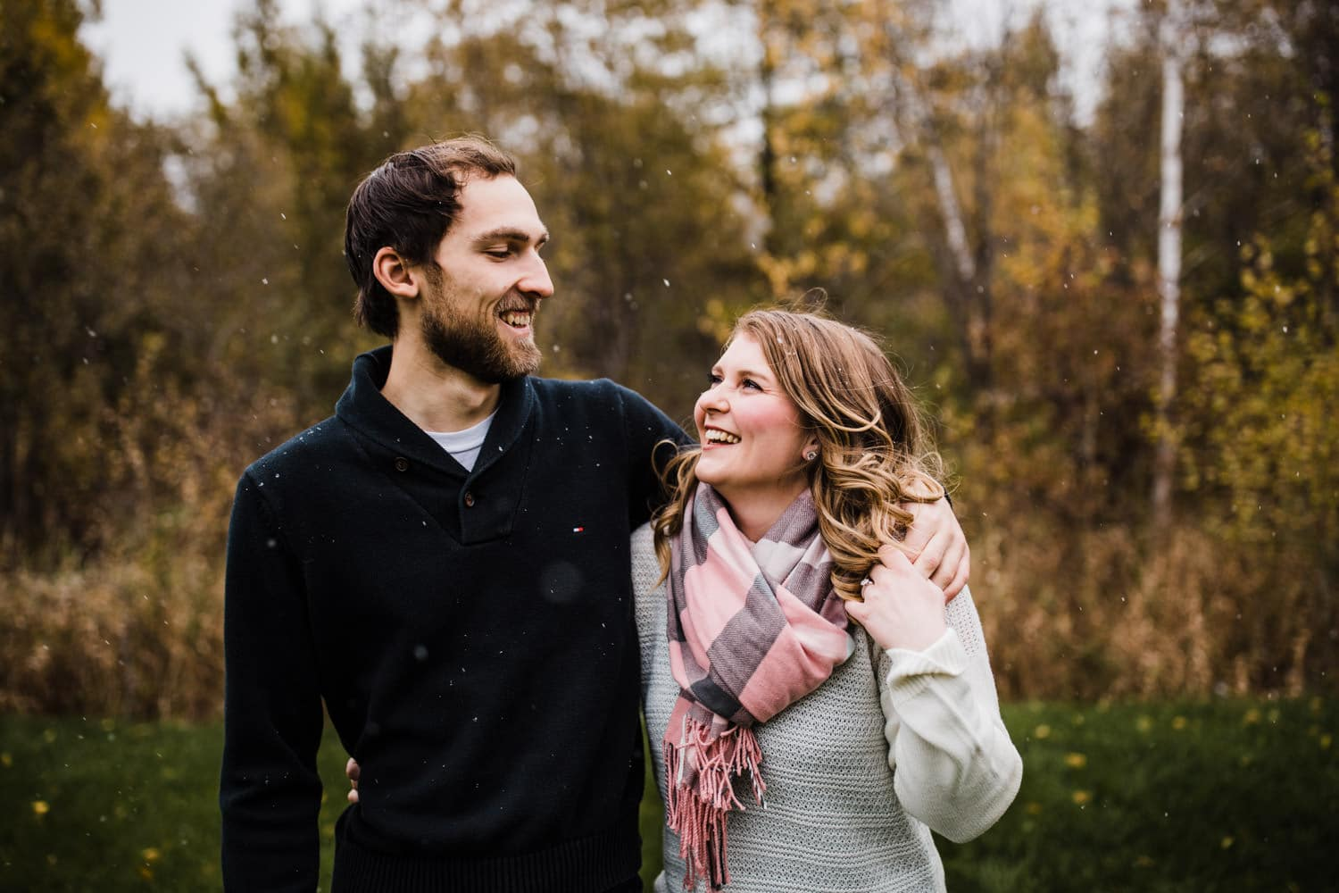 couple laugh during snowfall - ottawa winter engagement photos