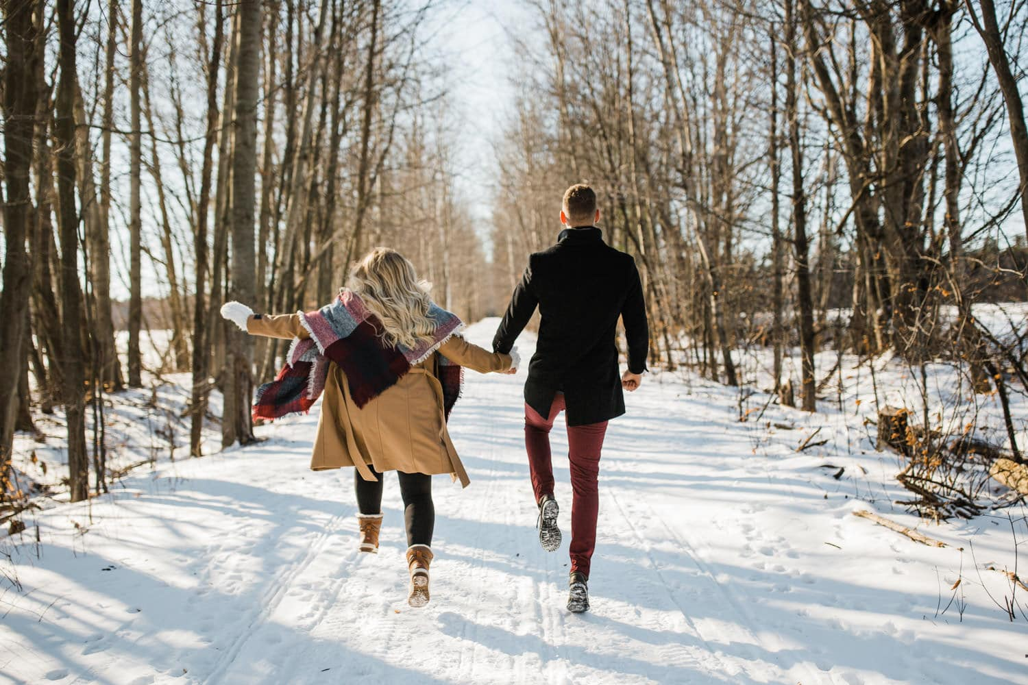 couple skip outside in winter - ottawa winter engagement photos