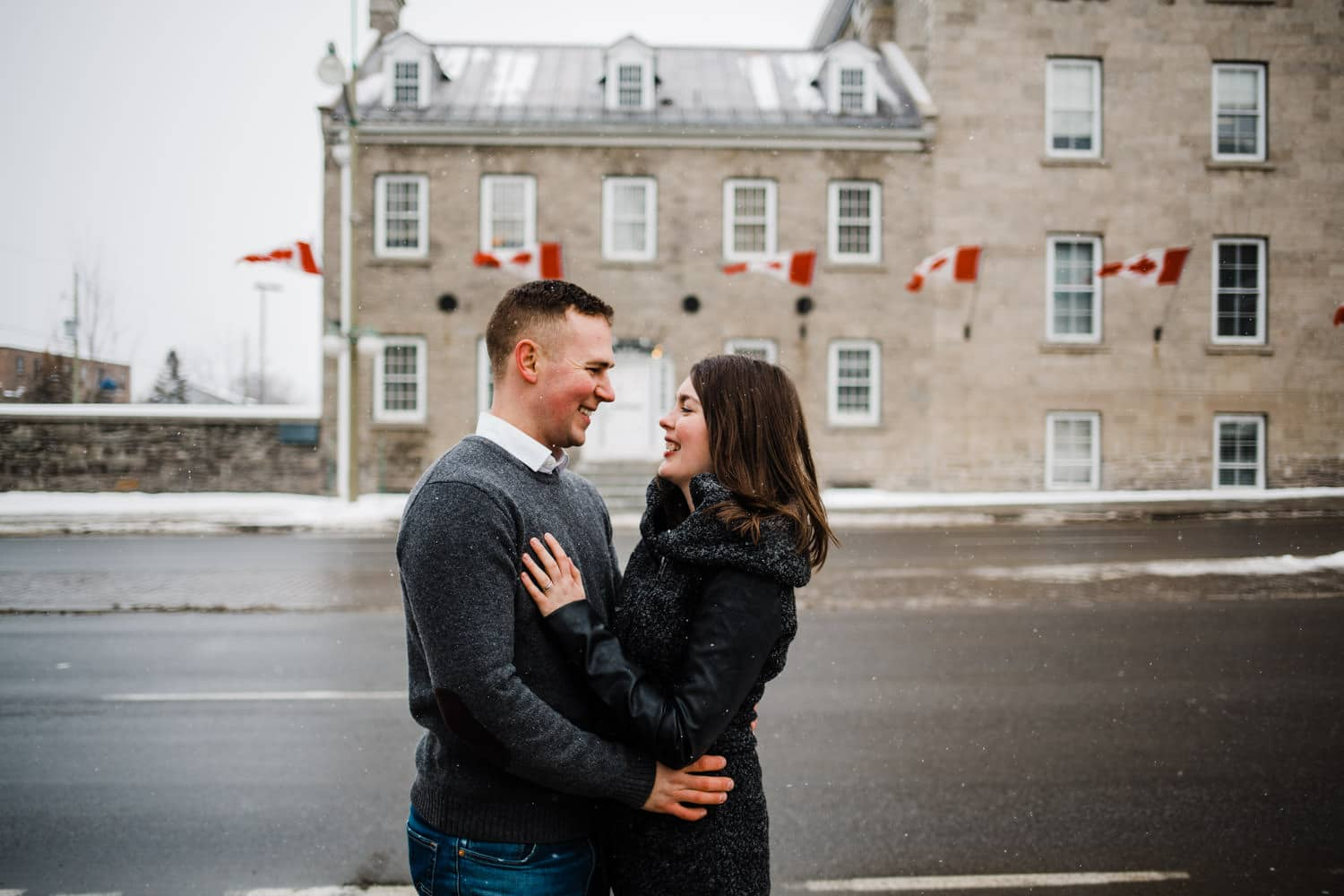 couple stand by snowy street - ottawa winter engagement photos