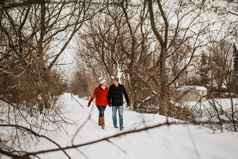 couple walk along pathway - ottawa winter engagement photos