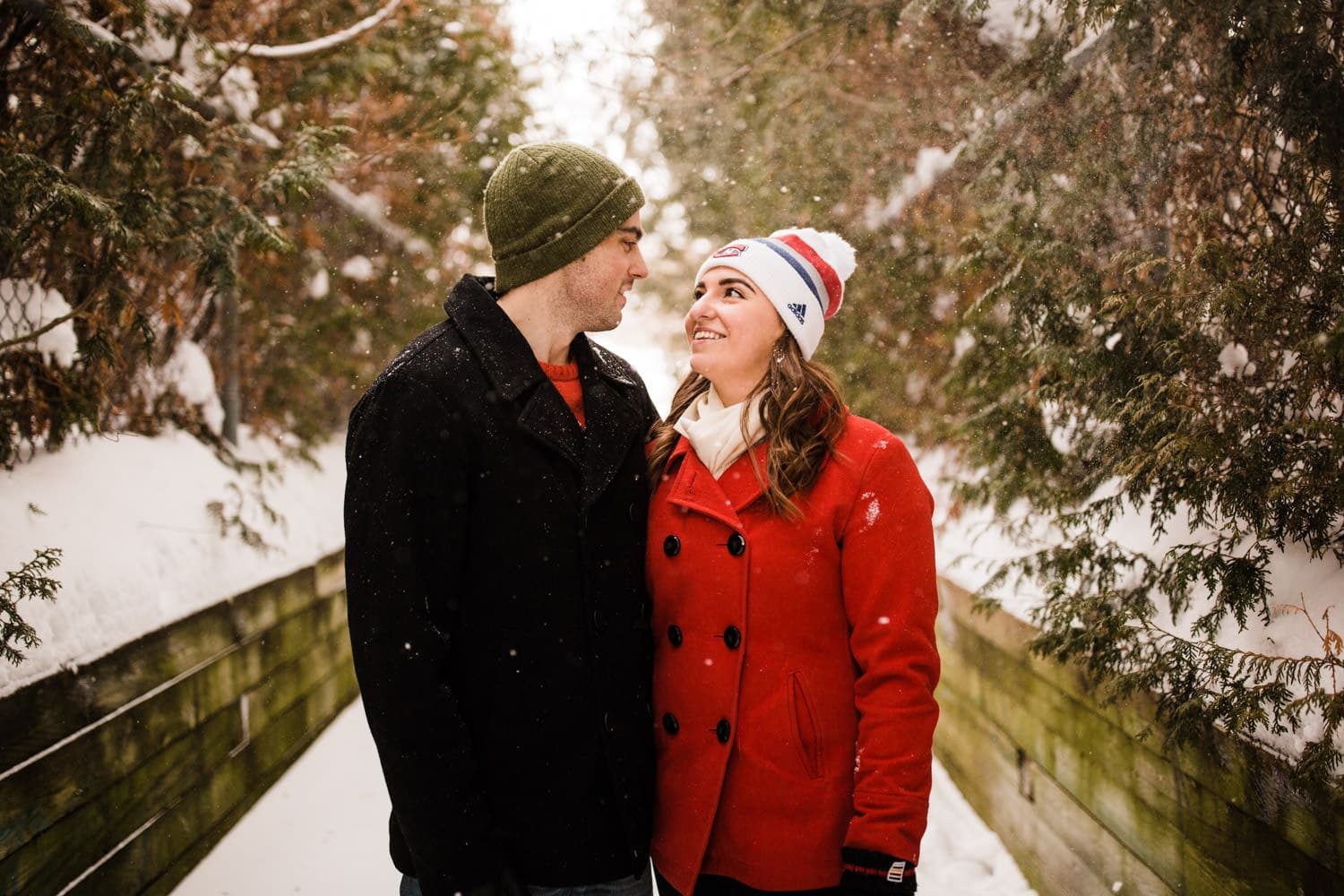 couple stand outside during snowfall - ottawa winter engagement photos
