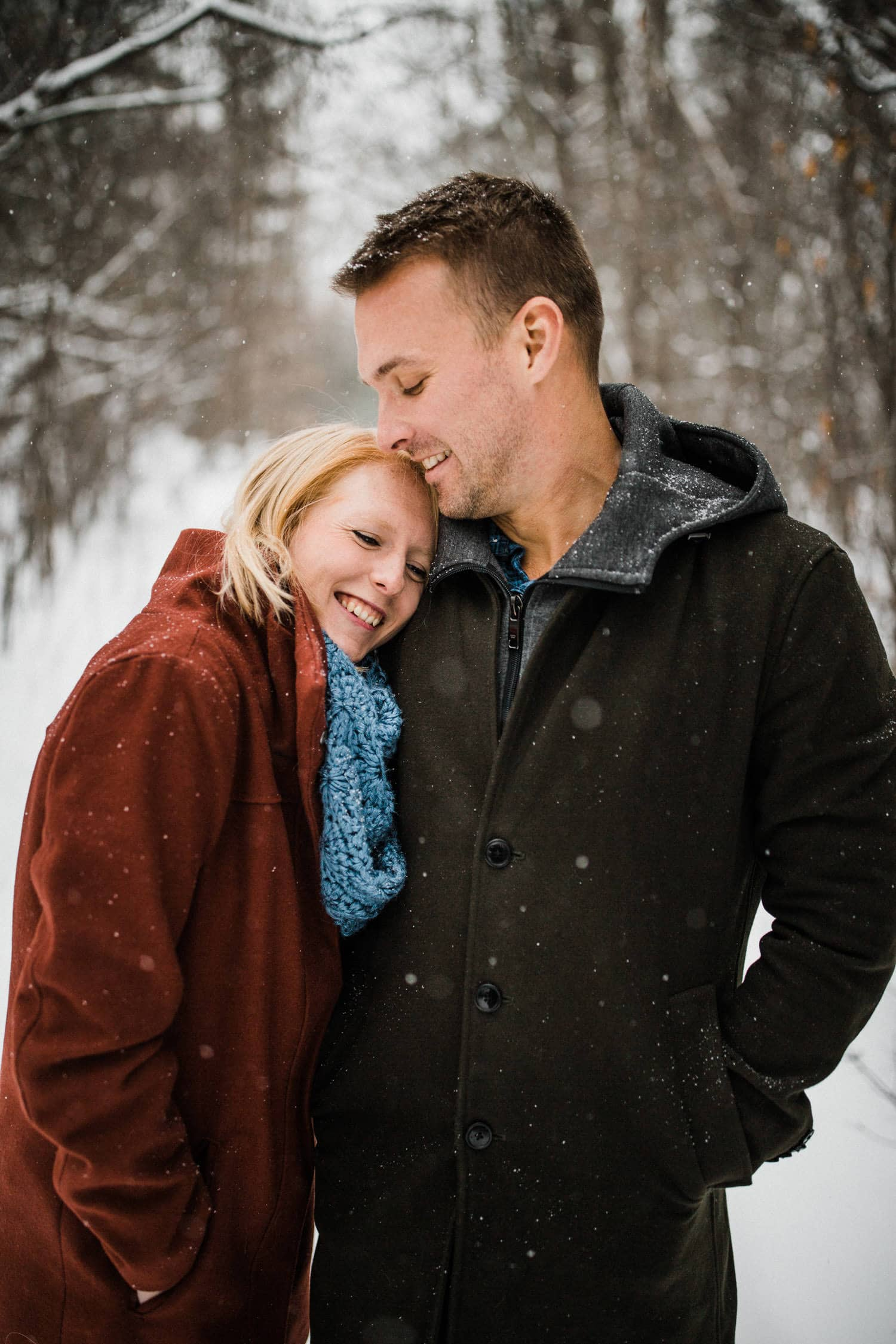 couple stand together outside during snowfall - ottawa winter engagement photos