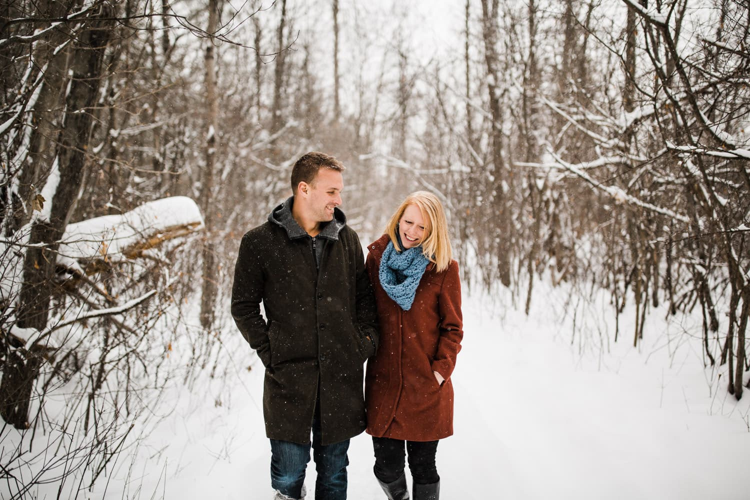 couple walk along snowy path - ottawa winter engagement photos