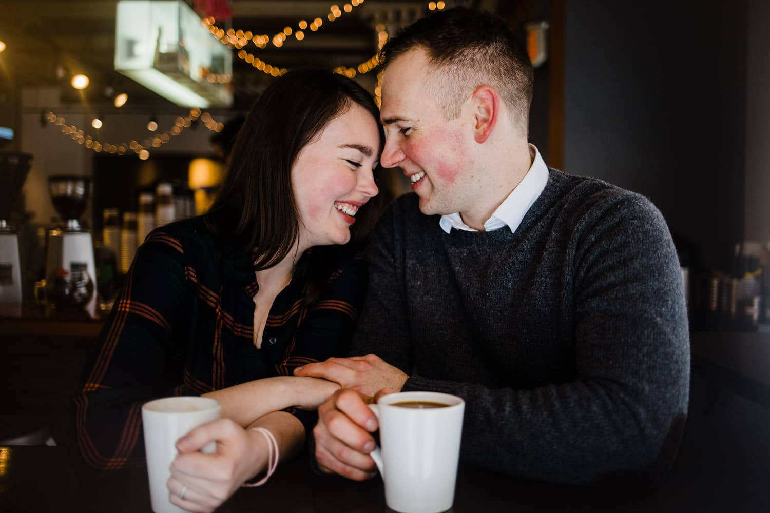 couple warm up in coffee shop - ottawa winter engagement photos