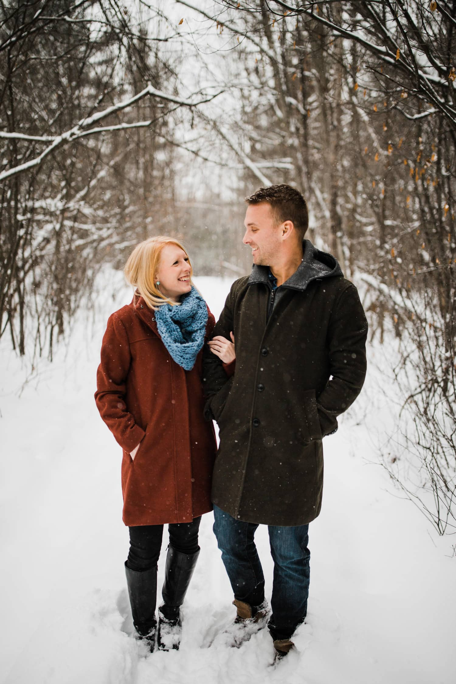 couple stand on snowy pathway - winter engagement in ottawa