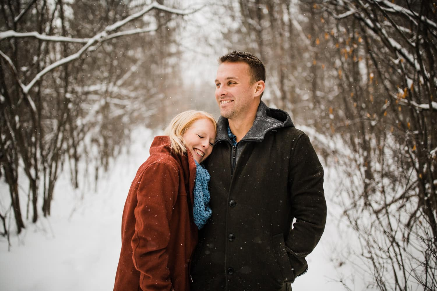 couple laugh together in snowfall - winter engagement in ottawa