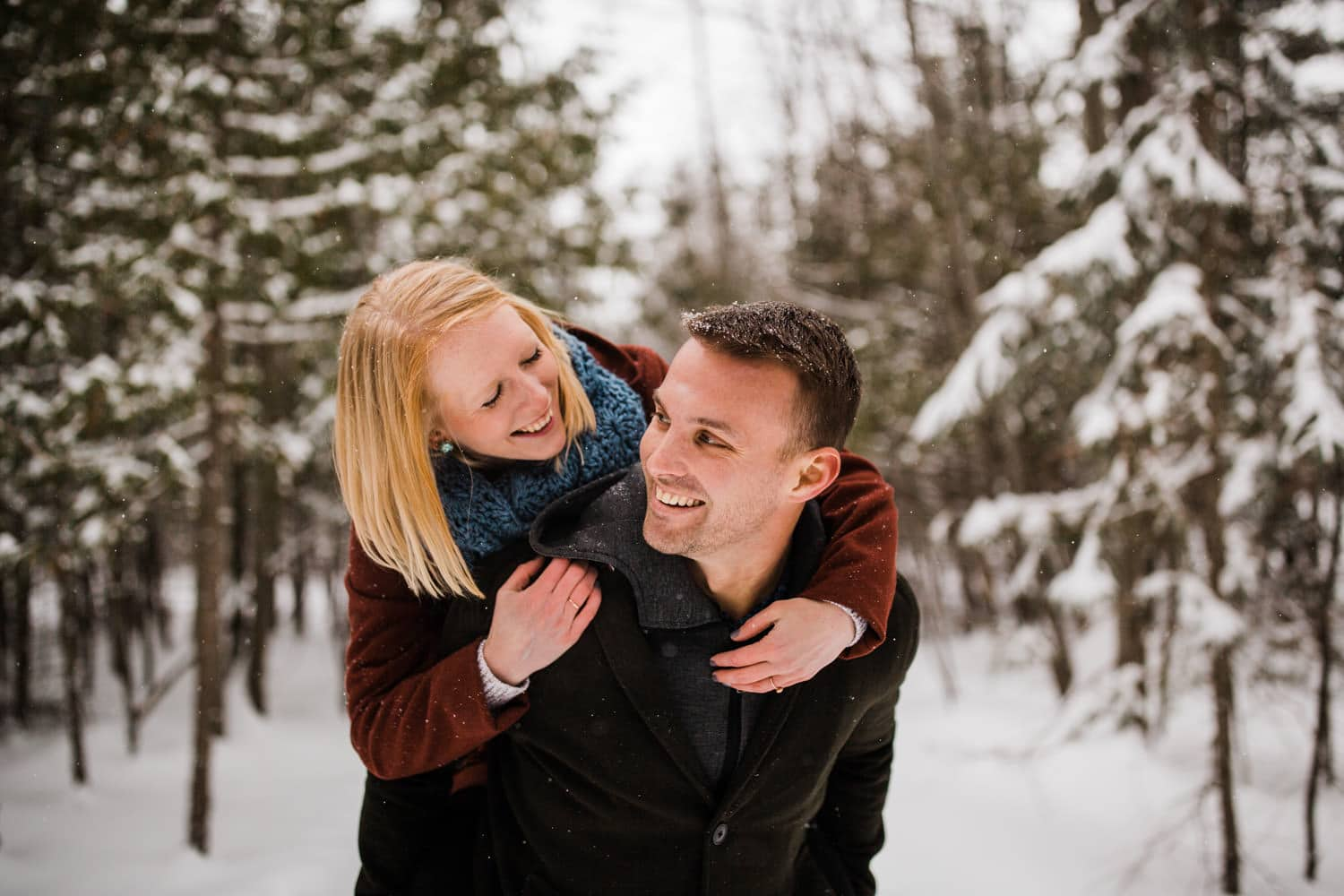 man gives woman piggy back outside during snowfall - winter engagement in ottawa