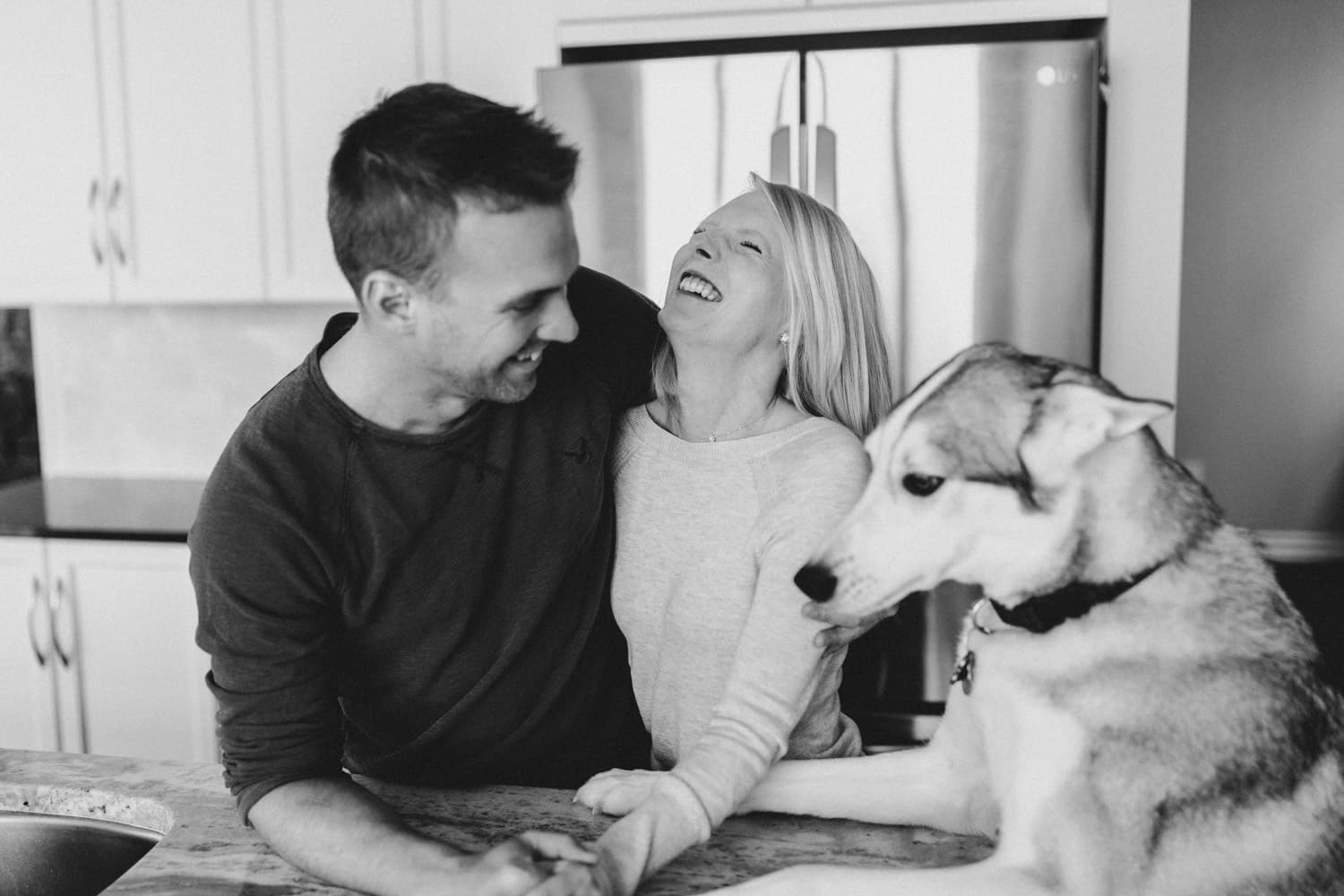 couple laughs as pet husky joins photo - at home engagment