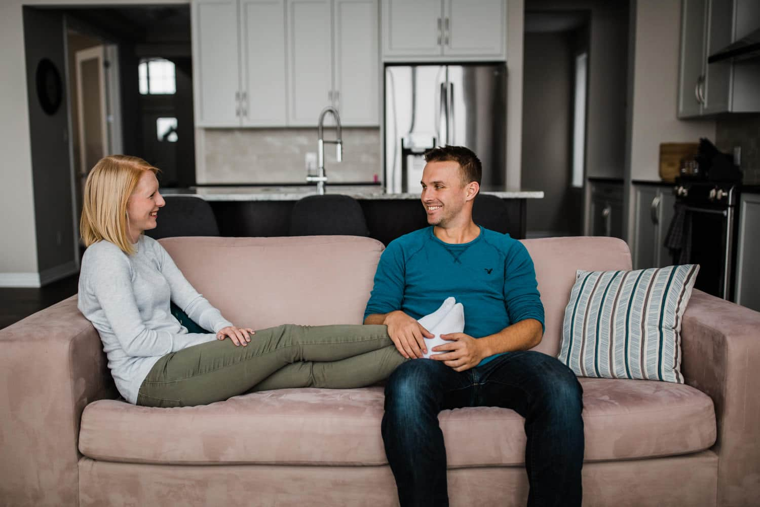 couple sits on couch together at home - at home engagement