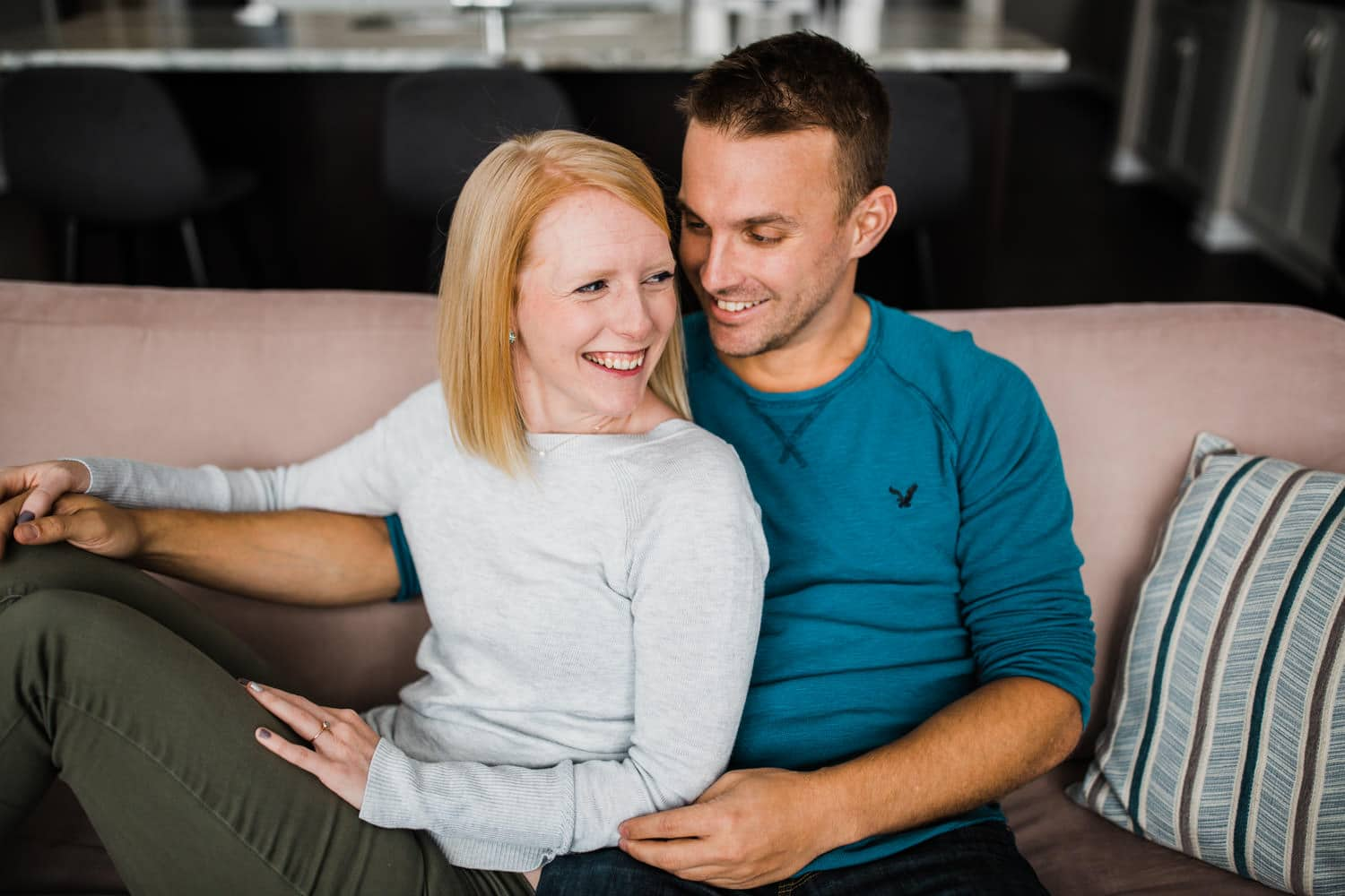 couple sit on couch together at home - at home engagement