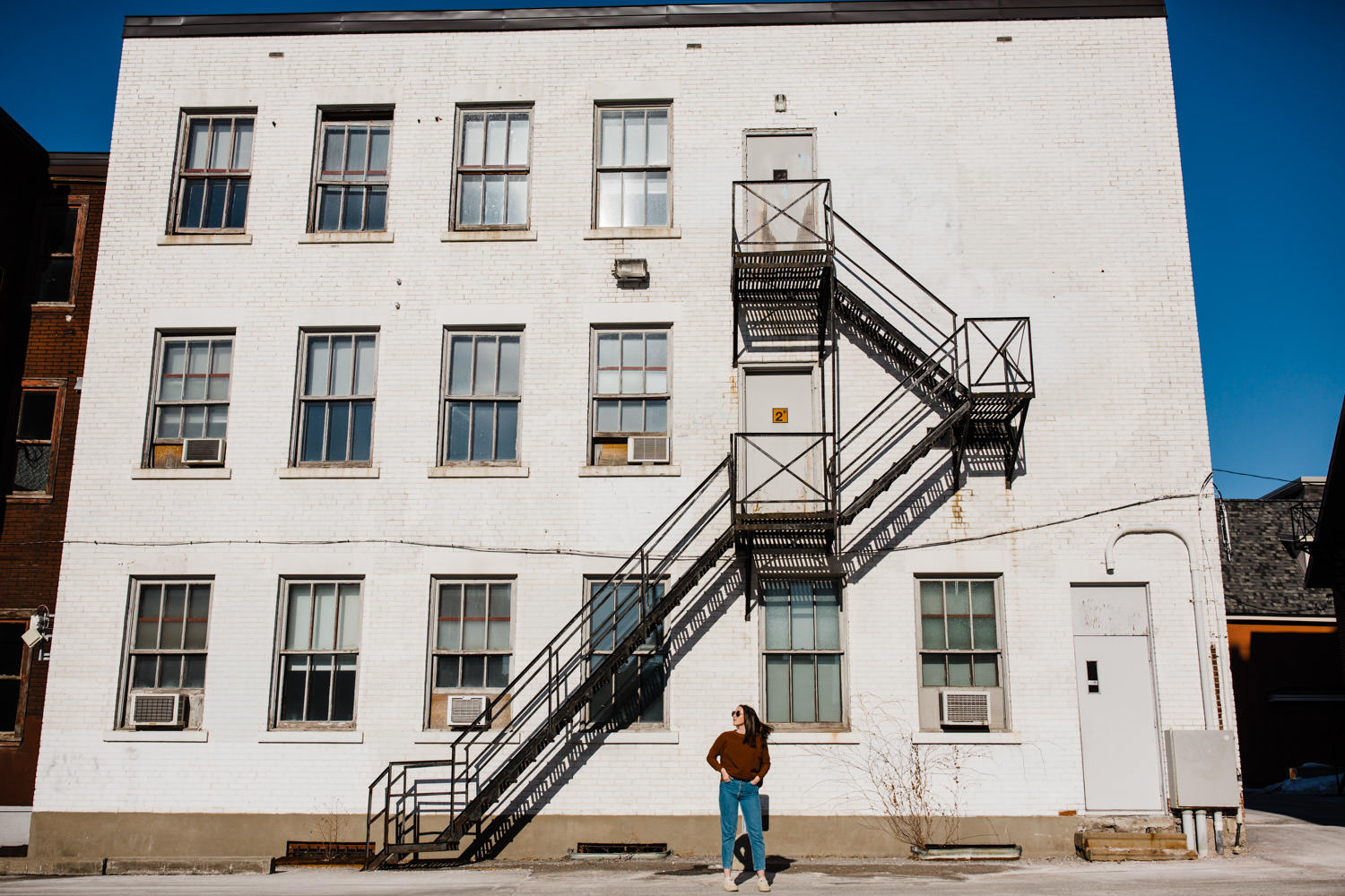 woman stands in front of a white building with a fire escape