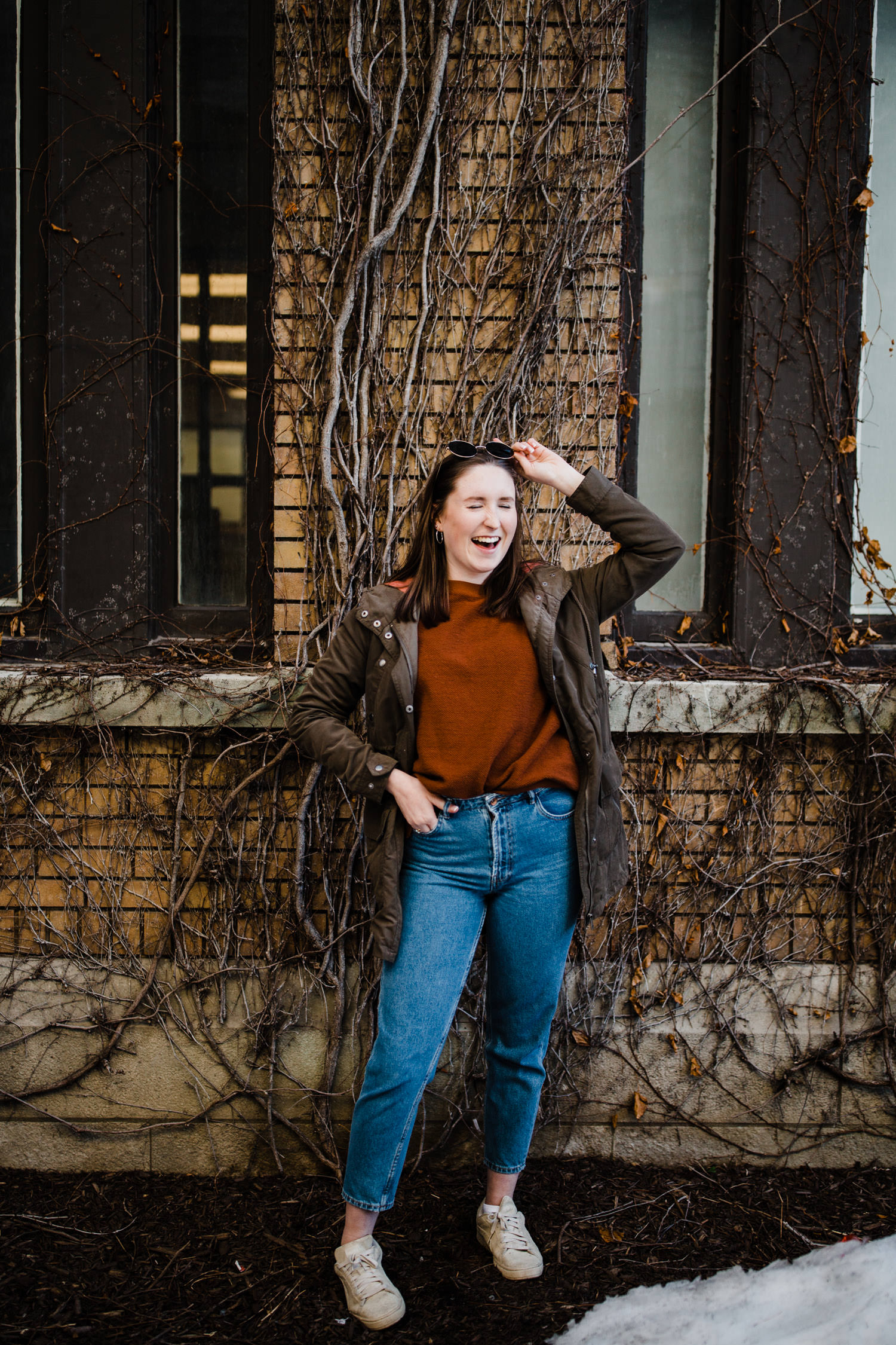 woman laughs in front of vine covered brick wall