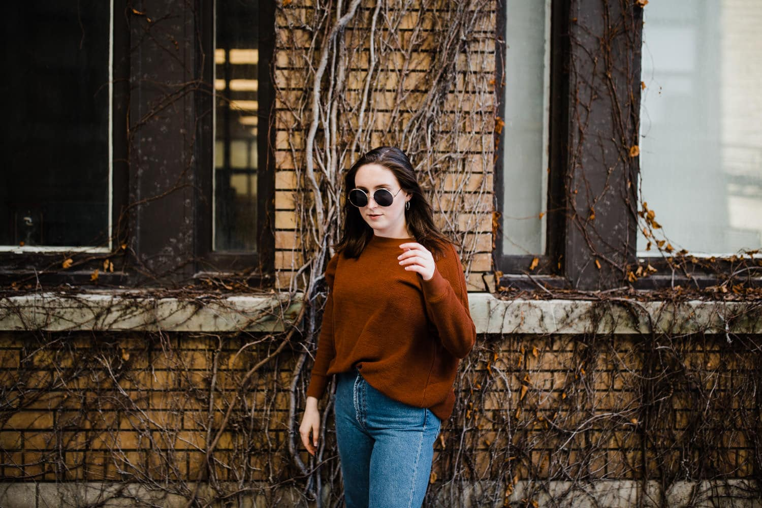 woman stands in front of vine covered wall wearing sunglasses