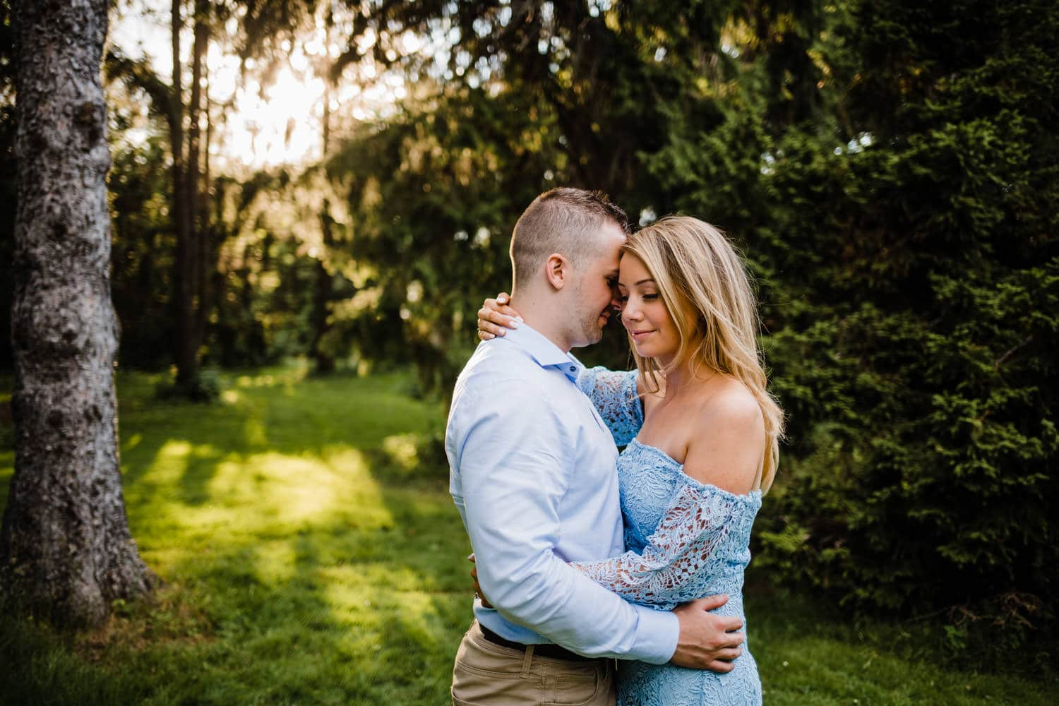 couple stand amongst trees - ottawa golden hour engagement session