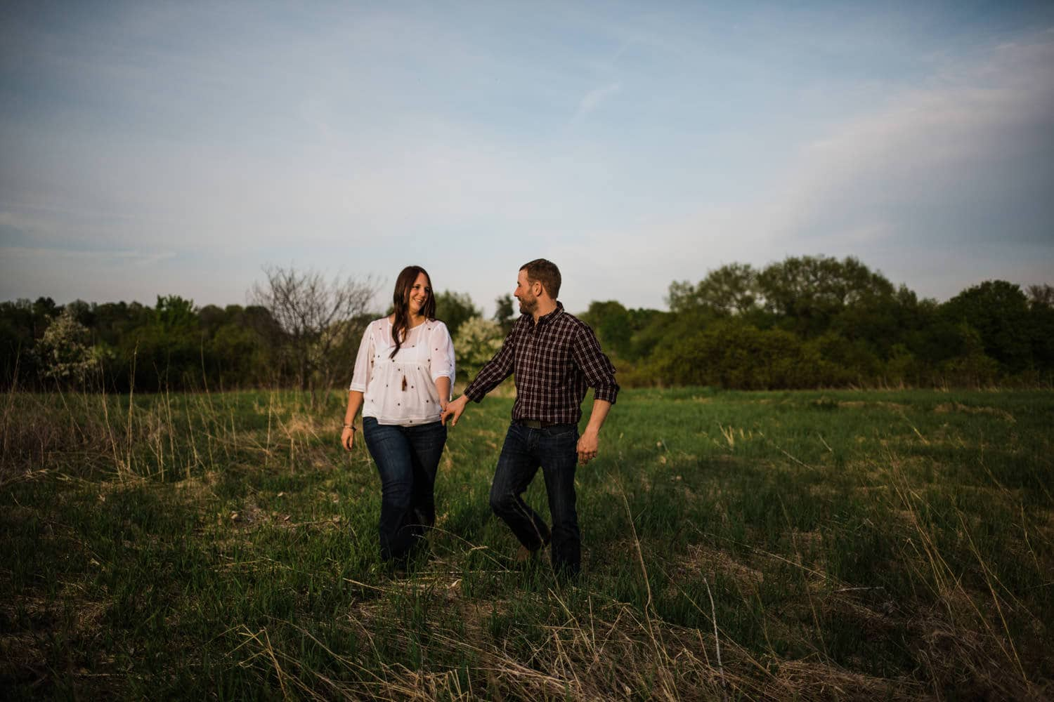 couple walk hand in hand during ottawa golden hour engagement session