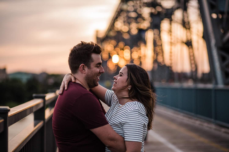 couple hug on alexandra bridge - ottawa golden hour engagement session