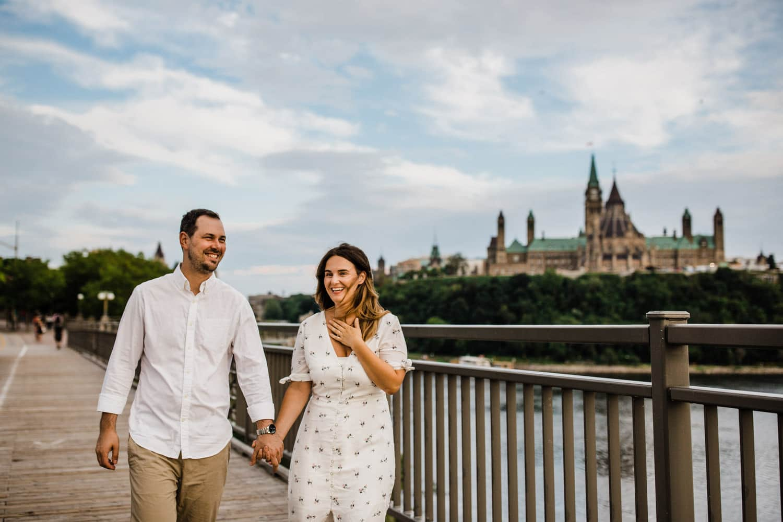couple walk alexandra bridge - ottawa golden hour engagement session