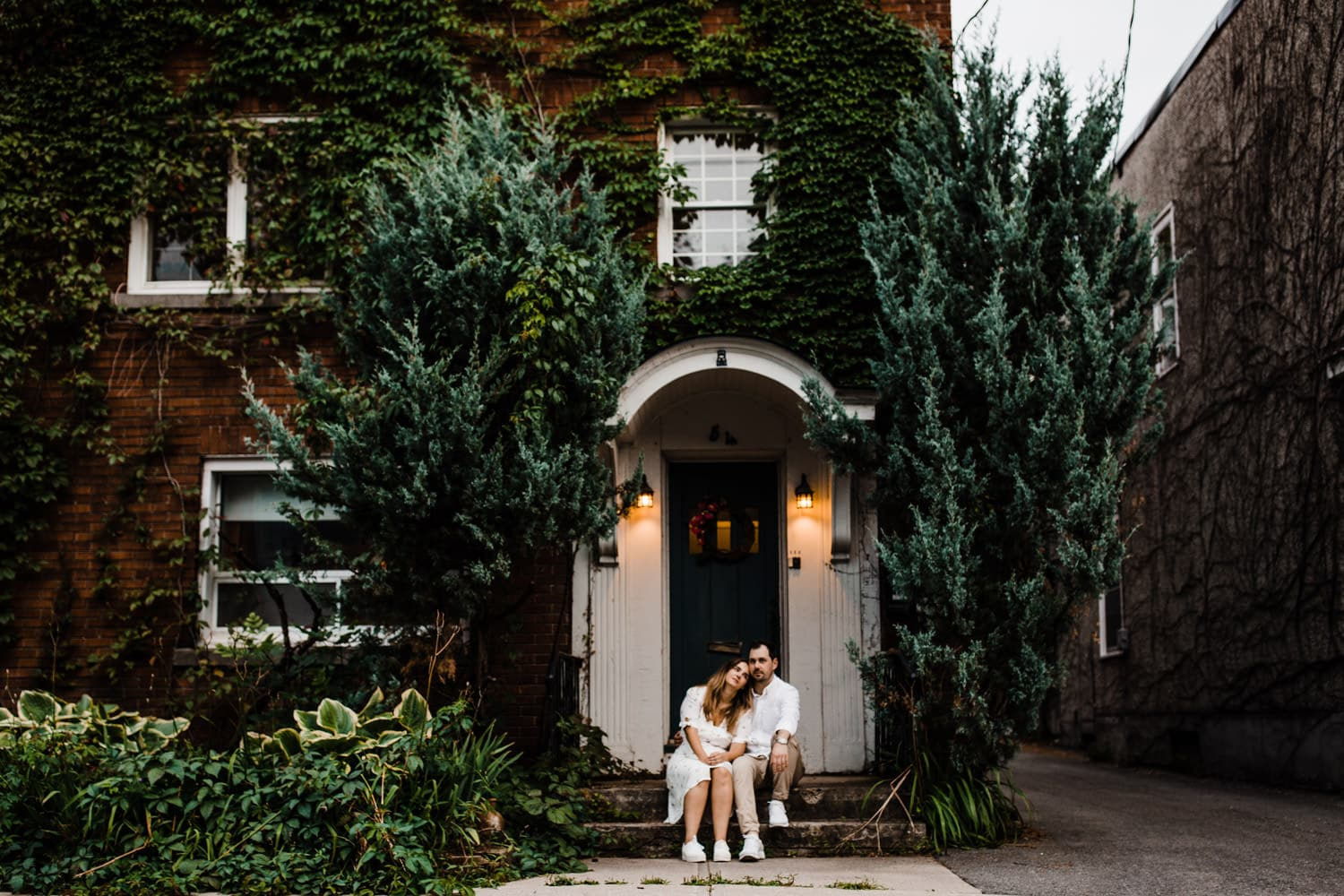 couple sit in front of vine covered home - ottawa golden hour engagement session
