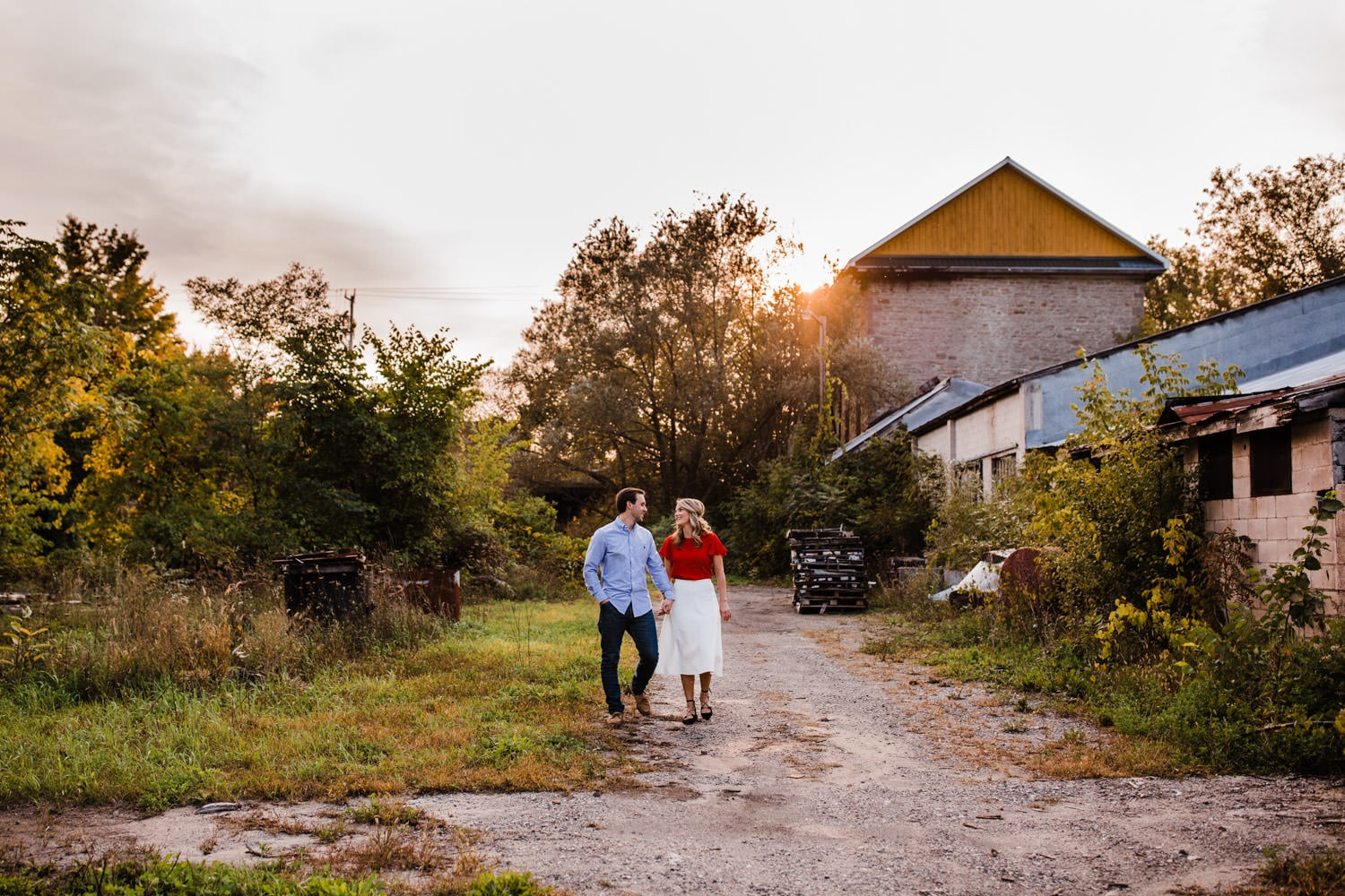 couple walk through industrial area - ottawa golden hour engagement session