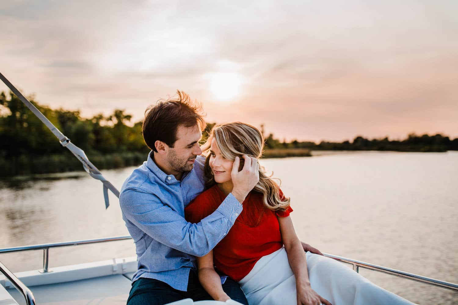 couple watch sunset from boat - ottawa golden hour engagement session