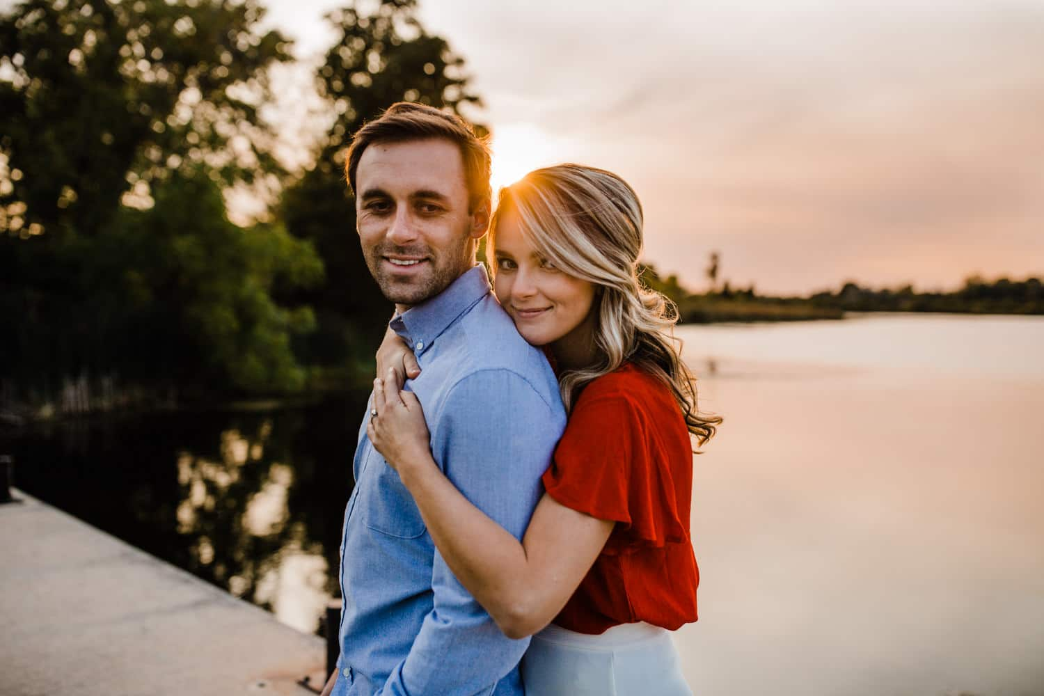 couple stand on dock as sun sets - ottawa golden hour engagement session