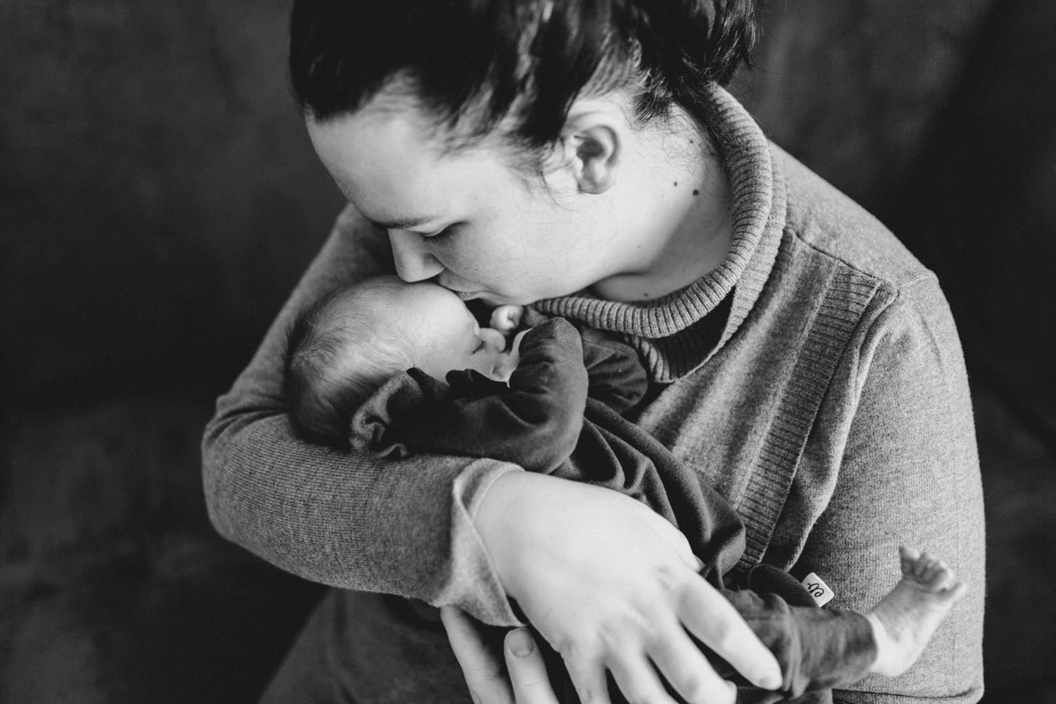 mom kisses baby girl on forehead - lifestyle newborn session