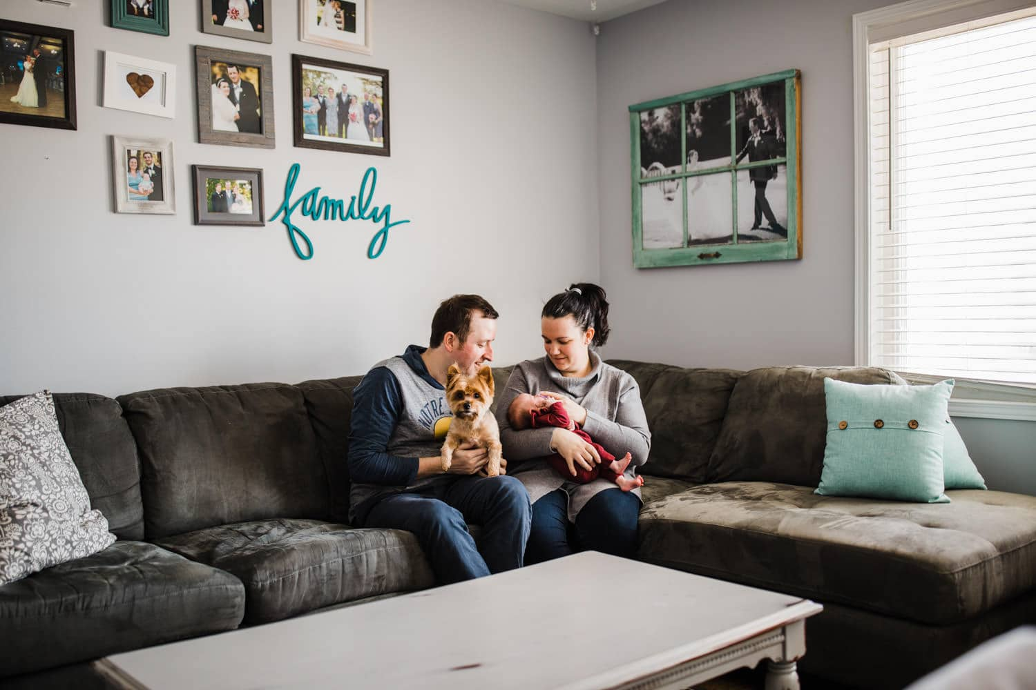 new parents sit in living room with newborn daughter and their dog - lifestyle newborn session