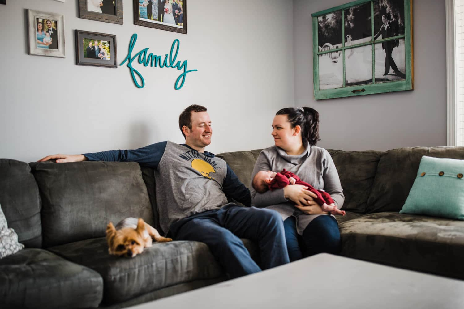 new parents sit together with baby in living room