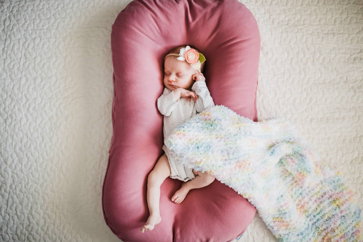 newborn baby sleeps in snuggle me organic pillow