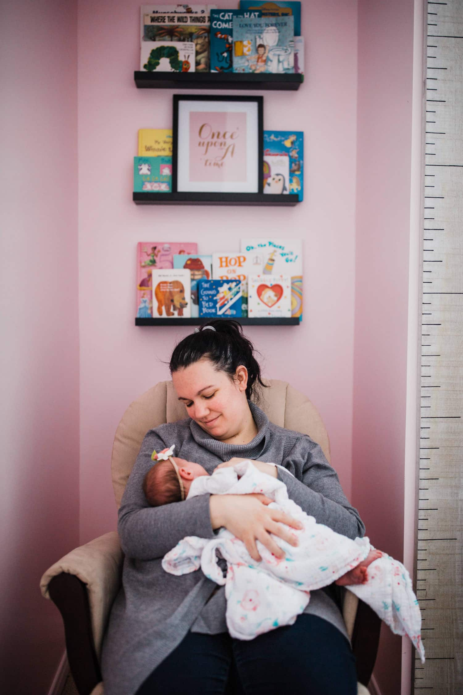 mom rocks newborn baby in nursery - lifestyle newborn session