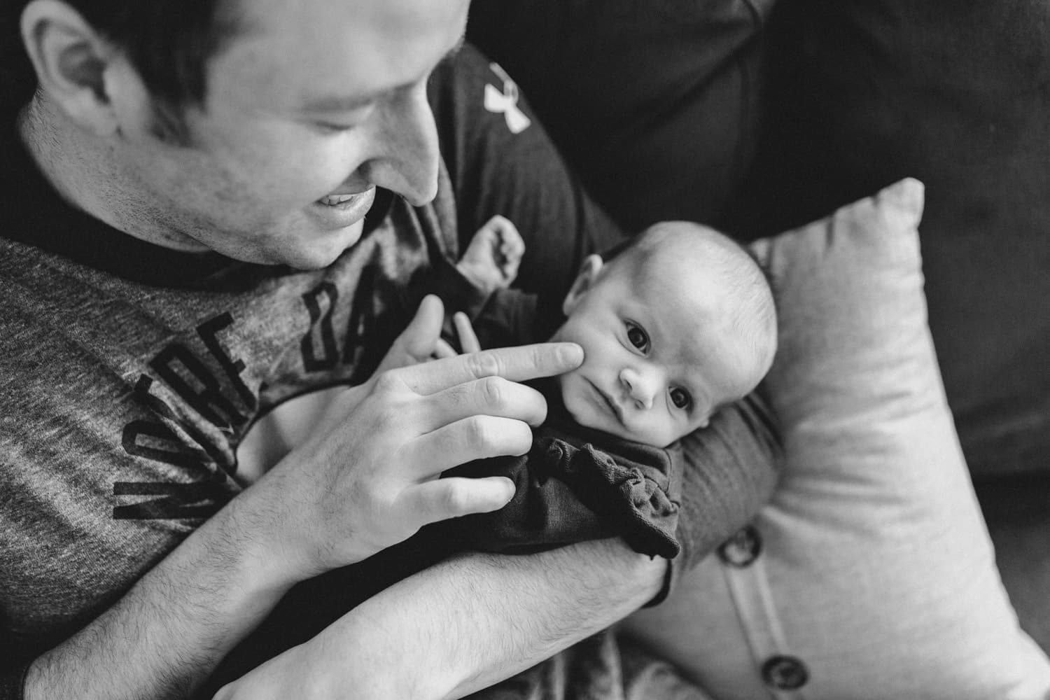 dad sits with newborn girl at home - lifestyle newborn session