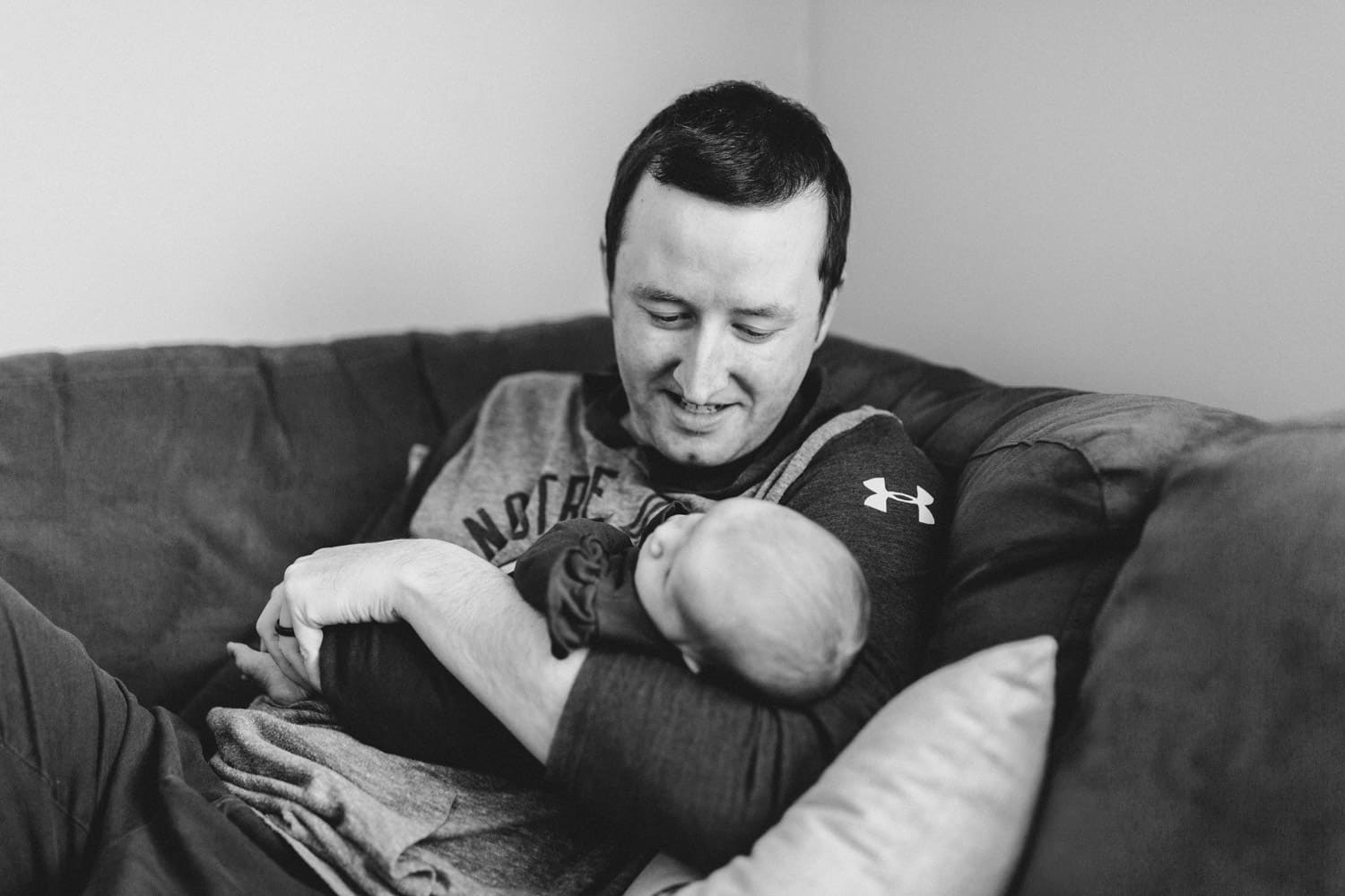 new dad sits with baby on the couch - lifestyle newborn session