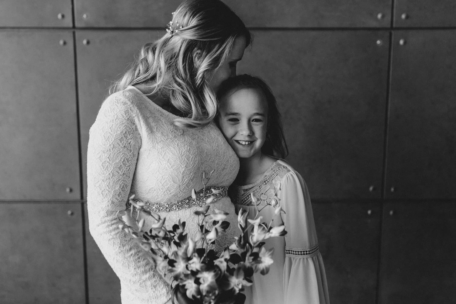 bride kisses her daughter's head on wedding day